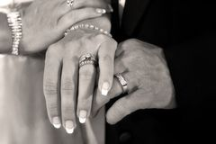 Forever. Bride and groom hold hands and show off their rings Stock Photos