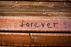 Forever. Word forever written with a black marker on the wooden background stock photos