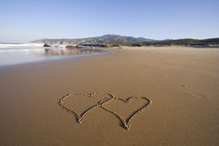 Forever love. Tho heart shapes writed on the beach sand stock photos
