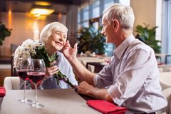 Adorable mature couple showing love. Forever love. Sweet cheerful mature couple having date while smiling and men touching women face Stock Images