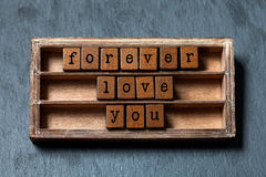 Forever love you message. Vintage box, wooden cubes phrase with old style letters. Gray stone textured background. Close. Up, up view, soft focus royalty free stock photos