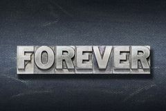 Forever word den. Forever word made from metallic letterpress on dark jeans background Royalty Free Stock Image