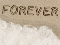Forever written in sand on the beach. Forever written in sand next to the shore on the beach. Friends/lovers/couples who have become enemies through deceit and Stock Photos