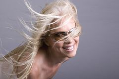 Forever Young. Beautiful anamorphic smiling blond girl in sunglasses with hair blowing in the wind Royalty Free Stock Photos