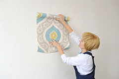 The forewoman glues wall-paper in the room Stock Image