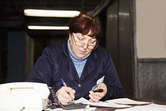 Forewoman writing at the desk Royalty Free Stock Images