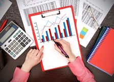 Forex chart. Businesswoman drawing forex chart on clipboard Stock Photography
