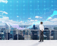 Forex charts. Businessman looking to forex charts and view on city Stock Images