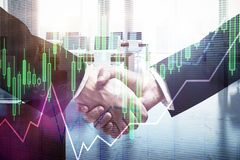 Forex concept. Close up of handshake with forex chart on blurry office interior background. Forex concept. Double exposure Royalty Free Stock Photography