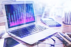 Forex and finance concept. Close up of laptop with business chart on screen place on office desktop. Forex and finance concept. Double exposure Royalty Free Stock Photography