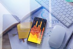 Forex and trade concept. Smartphone with business chart placed on office desktop with supplies and other items. City background. Forex and trade concept. Double Stock Image