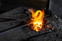 Forge. Blacksmith heats a decorative piece in the forge Royalty Free Stock Photo