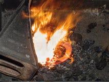 Forge avec les flammes fortes Les pinces tiennent la chaussure de cheval images stock