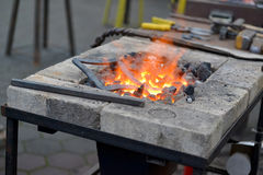 Forge brazier with tools and a metal detail Royalty Free Stock Photos