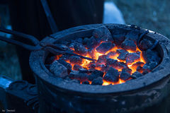 Forge horn with hot coals and metal horseshoe Royalty Free Stock Photography