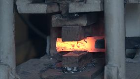 Forge hot metal. Making the knife out of metal at the forge. Close up blacksmith`s hands hitting hot metal with a massive hammer on an anvil stock footage