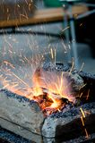 Forge. Sparks fly out of a primitive forge royalty free stock photo