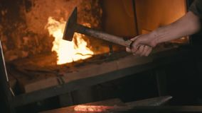 Forge workshop. Smithy manual production. Hands of smith with hammer hit on glowing hot metal, on the anvil, the forging