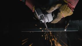 Close up details of sparks, industrial worker using angle grinder and cutting steel. Sparks fly straight in the camera stock footage