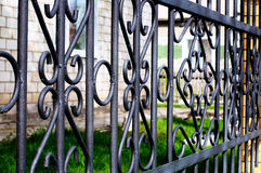 Forged black fence. Decorative forged black iron fence with twisted metal lines royalty free stock photo