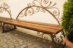 Forged brown wooden bench in the park with cobbles Stock Images