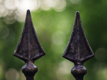 Forged decorative metal fence elements on a blurred background. Forged decorative metal fence elements on a blurred green background stock photo