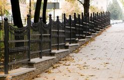 Forged fence in autumn street. Perspective forged fence in the autumn street of the city Stock Images