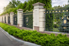 Forged fence painted with gold at entrance to luxury villa. Beautiful forged fence painted with gold at entrance to luxury villa stock photo