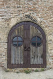 Forged gate in the brick wall. Wooden door forged with iron in the brick wall Royalty Free Stock Image