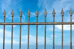 Forged iron fence with arrows. Close-up of a forged iron fence with arrows with blue sky and clouds Stock Images