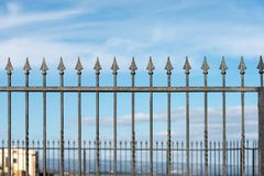 Forged iron fence with arrows. Close-up of a forged iron fence with arrows with blue sky and clouds Royalty Free Stock Photos