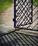 Forged iron gate open with shadow Royalty Free Stock Photos