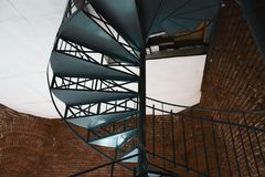 Forged iron twisted stairs with reflection on a red brick wall stock images