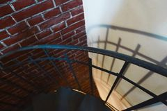 Forged iron twisted stairs with reflection on a red brick wall, handrails of the old vintage building, art royalty free stock photos