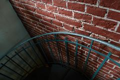 Forged iron twisted stairs with reflection on a red brick wall, handrails of the old vintage building, art stock photo