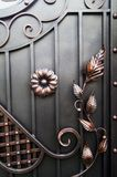 Forged items decorating modern metal gates. Forged metal gate elements. Decorative processing of metal gates Royalty Free Stock Image