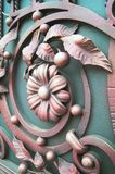 Forged items on green metal gates. Beautiful forged metal gates. Metal flowers, leaves of plants. Decoration of the gate Stock Images