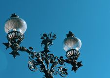 Forged lamp on blue sky background stock images