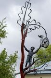 Forged metal sculpture `a boy climbs a tree and releases a bird from a cage.` st. Georgievskaya. stock photos