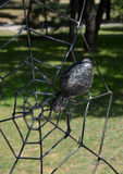 Forged metal spider on a web of wires Stock Image