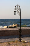 Forged park street lantern  on the beach with a boats Royalty Free Stock Images