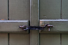 Forged steel hook on the green door Royalty Free Stock Photo