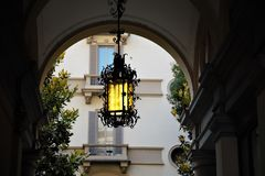 Forged street lamp with yellow glass. stock image
