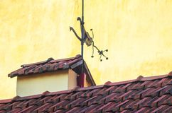 Forged Weather Vane on the Old Roof from Tiles. Forged Weather Vane on the Roof. Old Red Ceramic Roof Tiles Background. Old Pitched Roof. Roof Ridge stock photography