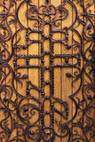 Forged wooden door with a cross in the church Royalty Free Stock Photography
