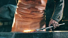 A forger hits hot knife with a metal hammer. Blacksmith forging iron in workshop. A forger hits hot knife with a metal hammer. 4K stock footage