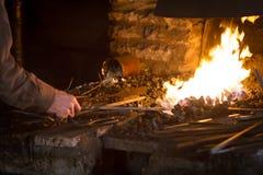Forgeron chauffant une tige en métal Image libre de droits