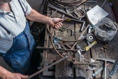 Forgeron faisant le fer travaillé avec la machine industrielle d'équipement de cintreuse pour le recourbement en métal photo stock