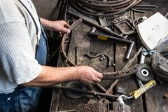 Forgeron faisant le fer travaillé avec la machine industrielle d'équipement de cintreuse pour le recourbement en métal photos libres de droits