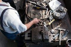 Forgeron faisant le fer travaillé avec la machine industrielle d'équipement de cintreuse pour le recourbement en métal photo libre de droits